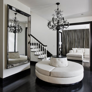 Large trendy black floor and painted wood floor foyer photo in Montreal with white walls