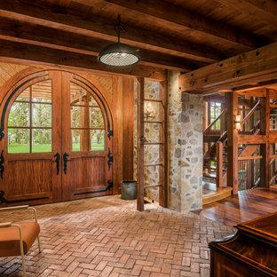 Idée de décoration pour un hall d'entrée champêtre avec un sol en brique, une porte double et une porte en bois brun.