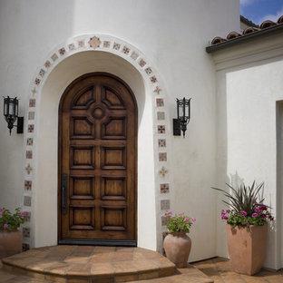 Inspiration for a mediterranean terra-cotta floor entryway remodel in Orange County with a dark wood front door