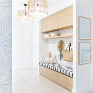 This is an example of a mid-sized beach style mudroom in Gold Coast - Tweed with white walls, a single front door, a white front door and beige floor.