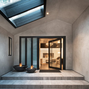 Example of a trendy entryway design in Santa Barbara with a glass front door and gray walls