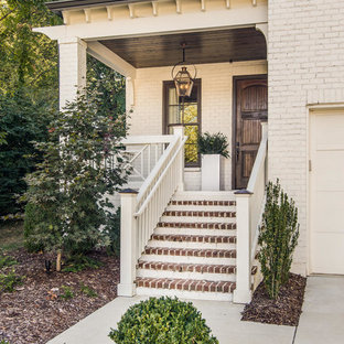 Example of a classic entryway design in Nashville with white walls and a dark wood front door