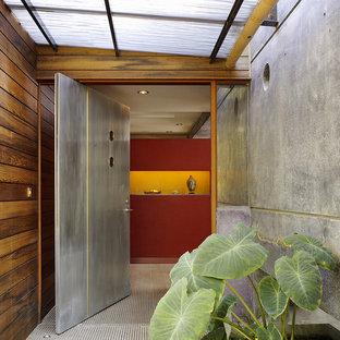 Ejemplo de puerta principal contemporánea, grande, con paredes rojas, suelo de cemento, puerta pivotante y puerta metalizada