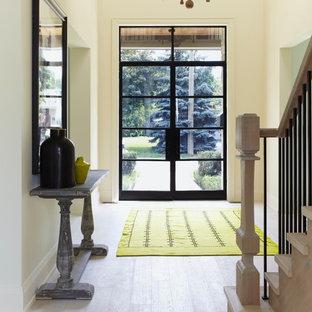 トロントの中サイズの両開きドアコンテンポラリースタイルのおしゃれな玄関ドア (ベージュの壁、淡色木目調のドア、ラミネートの床、ベージュの床) の写真