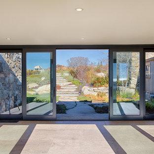 Foto de puerta principal costera, extra grande, con suelo de cemento, puerta corredera, puerta de vidrio y suelo gris