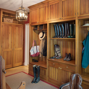 Example of a large classic medium tone wood floor and brown floor mudroom design in DC Metro with brown walls
