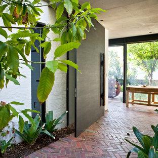 Ejemplo de puerta principal contemporánea con puerta pivotante, suelo de ladrillo y suelo rojo