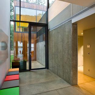 Cette photo montre une entrée moderne avec béton au sol.