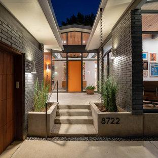 Idee per un piccolo ingresso moderno con una porta singola e una porta arancione