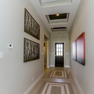Example of a large transitional laminate floor and beige floor entryway design in Houston with beige walls and a glass front door