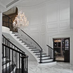 Aménagement d'un très grand hall d'entrée classique avec un mur blanc, un sol en marbre, une porte double et une porte noire.