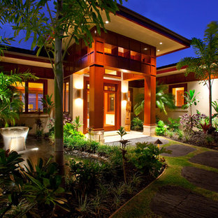 Large arts and crafts travertine floor entryway photo in Hawaii with orange walls and a dark wood front door