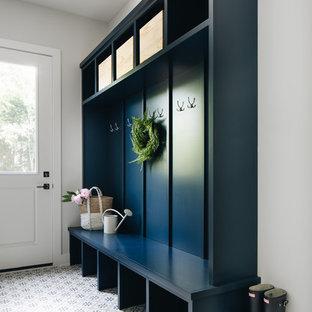 Idée de décoration pour une entrée marine avec un vestiaire, un mur gris, une porte simple, une porte blanche et un sol multicolore.