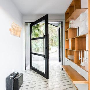 Retro inredning av en stor hall, med vita väggar, en pivotdörr, glasdörr, flerfärgat golv och klinkergolv i porslin