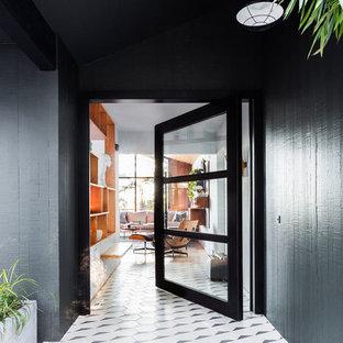На фото: большая входная дверь в стиле ретро с поворотной входной дверью, стеклянной входной дверью, черными стенами, полом из керамогранита и белым полом с