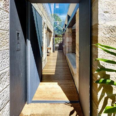 Trendy light wood floor and brown floor entryway photo in Sydney with a metal front door and brown walls