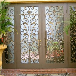 Large tuscan brick floor entryway photo in Miami with a metal front door and beige walls