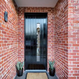 アデレードの大きい片開きドアコンテンポラリースタイルのおしゃれな玄関ドア (赤い壁、磁器タイルの床、濃色木目調のドア、グレーの床) の写真