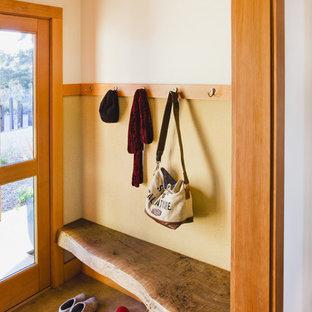 Exemple d'une entrée nature avec un vestiaire, un mur beige, une porte simple et une porte en verre.