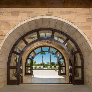 Tuscan entryway photo in San Diego with a glass front door