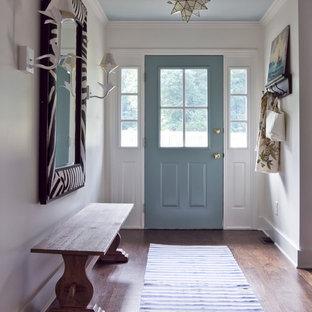 Aménagement d'une entrée éclectique avec un couloir, une porte simple, une porte bleue et un sol marron.