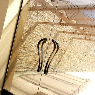 オレンジカウンティの巨大な両開きドアコンテンポラリースタイルのおしゃれな玄関ロビー (ベージュの壁、テラゾーの床、ガラスドア、マルチカラーの床) の写真