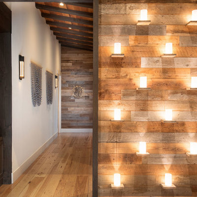 Example of a large mountain style medium tone wood floor and brown floor entryway design in Other with white walls and a dark wood front door