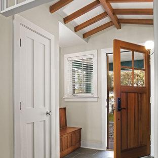 Idées déco pour une entrée classique avec une porte simple, une porte en bois brun et un sol en ardoise.