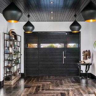 Diseño de puerta principal actual, de tamaño medio, con paredes blancas, suelo de madera oscura, puerta pivotante y puerta negra