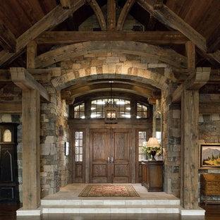 Cette photo montre un grand hall d'entrée montagne avec un mur beige, un sol en bois foncé, une porte double et une porte en bois foncé.