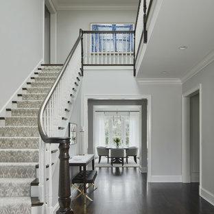Idée de décoration pour un hall d'entrée tradition avec un mur gris, un sol en bois foncé et un sol marron.