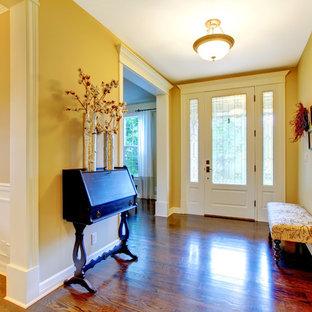Inspiration pour une porte d'entrée traditionnelle de taille moyenne avec un mur beige, un sol en bois foncé, une porte simple et une porte blanche.