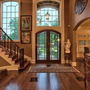 Foto di un ampio ingresso classico con pareti marroni, parquet scuro, una porta a due ante e una porta in legno scuro