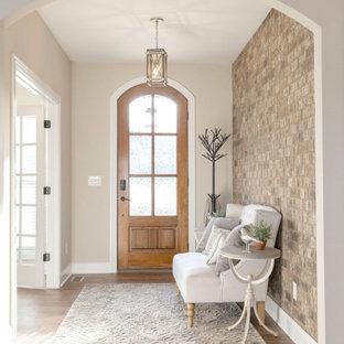 他の地域の広い片開きドアトランジショナルスタイルのおしゃれな玄関ロビー (ベージュの壁、無垢フローリング、木目調のドア、茶色い床、レンガ壁) の写真