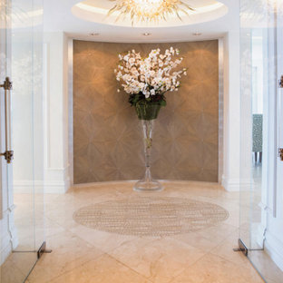 Entryway - large modern marble floor entryway idea in Miami with white walls and a glass front door