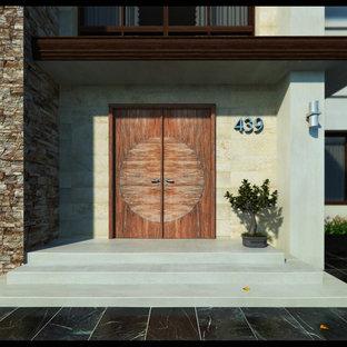 Entryway - mid-sized contemporary concrete floor entryway idea in Tampa with beige walls and a medium wood front door