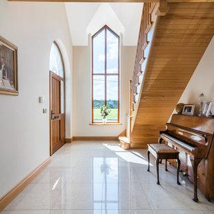 Ejemplo de hall clásico, grande, con puerta simple, puerta de madera en tonos medios, suelo de baldosas de porcelana, paredes beige y suelo blanco