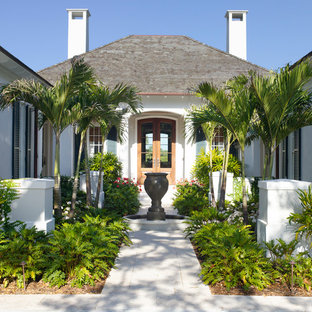 Example of a mid-sized island style entryway design in Miami with white walls and a medium wood front door