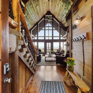 アトランタの中くらいの両開きドアラスティックスタイルのおしゃれな玄関ロビー (無垢フローリング、茶色い床、三角天井、板張り壁) の写真