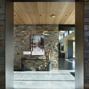 На фото: большое фойе в стиле рустика с разноцветными стенами, бетонным полом, серым полом, деревянным потолком и кирпичными стенами