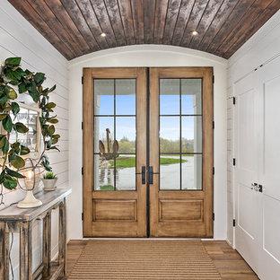 Idée de décoration pour une porte d'entrée champêtre avec un mur blanc, une porte double, un sol marron et une porte en verre.