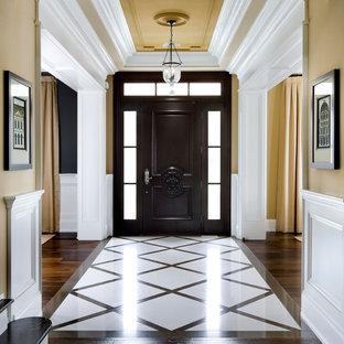 Aménagement d'une entrée classique avec un mur beige et un sol multicolore.