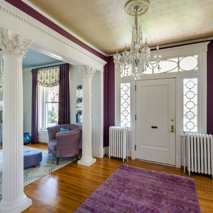 Example of a classic medium tone wood floor and brown floor entryway design in Richmond with purple walls and a white front door