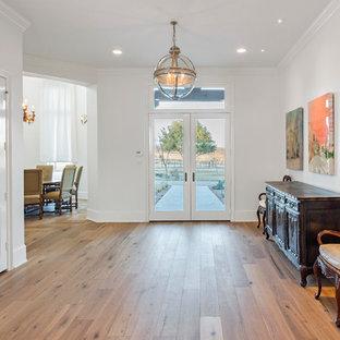Immagine di un grande ingresso contemporaneo con pareti bianche, pavimento in legno massello medio, una porta a due ante e una porta in vetro