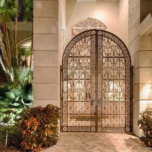 На фото: вестибюль в средиземноморском стиле с синими стенами, кирпичным полом, двустворчатой входной дверью, металлической входной дверью и оранжевым полом с