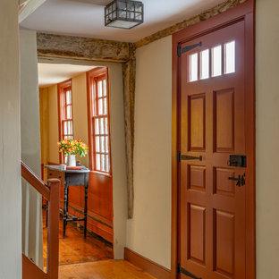 Idée de décoration pour une porte d'entrée champêtre de taille moyenne avec un mur blanc, un sol en bois brun, une porte simple et une porte rouge.