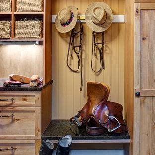 Réalisation d'une entrée chalet de taille moyenne avec un vestiaire, un mur marron, béton au sol, une porte simple, une porte en bois clair et un sol vert.