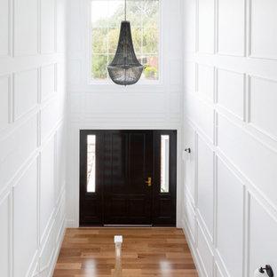 На фото: большая входная дверь в классическом стиле с белыми стенами, светлым паркетным полом, одностворчатой входной дверью, черной входной дверью и панелями на стенах с