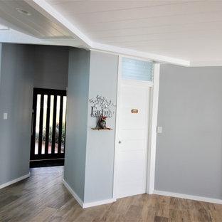 Bild på en stor maritim foajé, med grå väggar, ljust trägolv, en pivotdörr, glasdörr och beiget golv