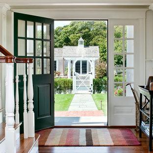 Esempio di un ingresso stile marino di medie dimensioni con pareti bianche, pavimento in legno massello medio, una porta a pivot e una porta verde